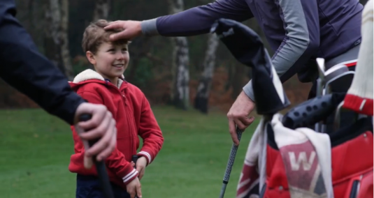 A golf player ruffles the hair of a young boy