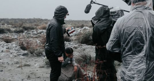 A team film in the rain, all wearing jackets