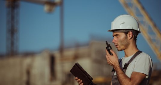 A man speaking into a walkie talkie on a construction site