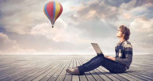 A man sits on the ground, working on a computer, looking at a hot air balloon in the sky