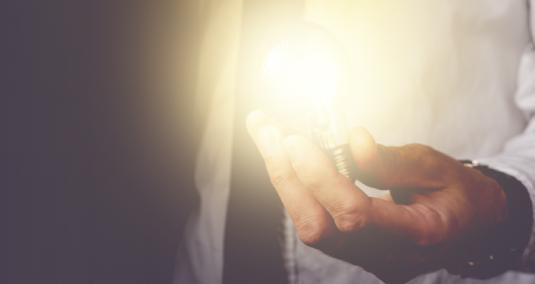 A man holds a lightbulb