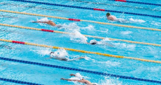 Five swimmers racing in swimming pool lanes