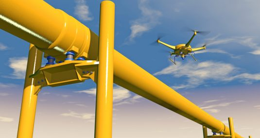 A drone flies over an industrial pipe