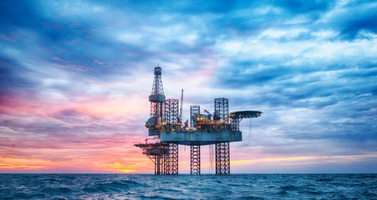An oil rig with sunset in the background